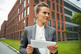 Business woman with tablet pc in front of office building