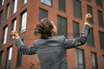 Business woman rejoicing in front of office building. rear view