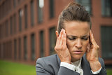Portrait of stressed business woman in front of office building