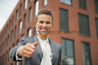 Portrait of happy business woman stretching hand for handshake i