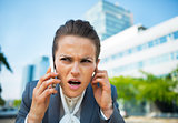 Portrait of concerned business woman talking cell phone in offic