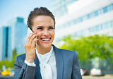 Smiling business woman talking cell phone in office district