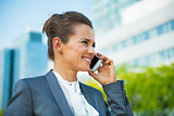 Smiling business woman talking cell phone in front of office bui
