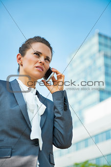 Business woman talking mobile phone in office district