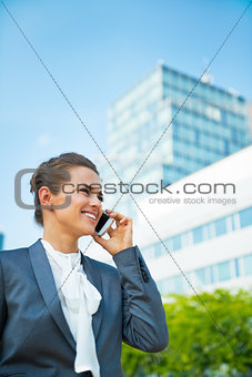 Smiling business woman talking mobile phone in office district