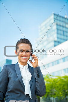 Smiling business woman talking mobile phone in front of office b