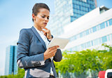 Thoughtful business woman with tablet pc in office district