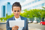 Serious business woman using tablet pc in office district
