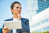 Portrait of thoughtful business woman in front of office buildin