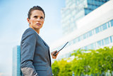 Portrait of confident business woman with tablet pc in office di