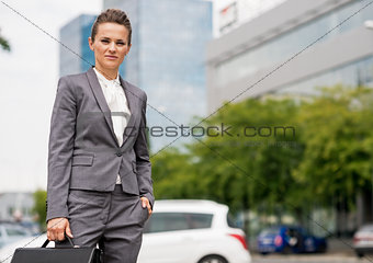 Portrait of business woman with briefcase standing in office dis