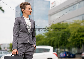Business woman with briefcase standing in office district and lo