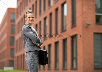 Portrait of smiling business woman in front of office building