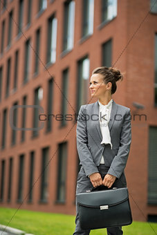 Business woman in front of office building looking on copy space