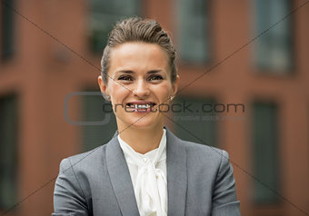 Portrait of happy business woman in front of office building