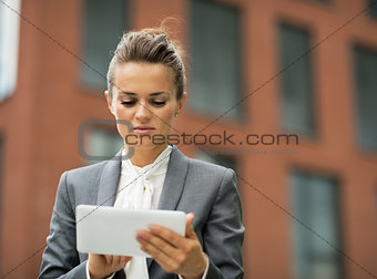 Business woman using tablet pc in front of office building