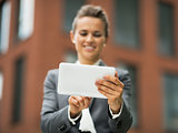 Closeup on business woman using tablet pc in front of office bui