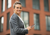 Smiling business woman with tablet pc in front of office buildin