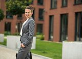 Portrait of business woman with briefcase in front of office bui