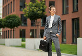 Business woman with briefcase in front of office building