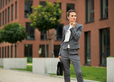 Thoughtful business woman with briefcase in front of office buil