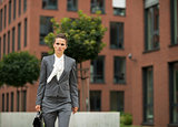 Business woman with briefcase walking in business district