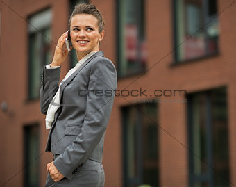 Business woman talking cell phone in front of office building