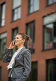 Happy business woman talking cell phone in front of office build