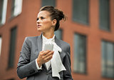 Portrait of business woman with cell phone in front of office bu