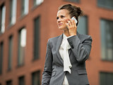 Business woman talking mobile phone in front of office building
