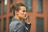 Serious business woman talking cell phone in front of office bui