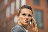 Portrait of serious business woman talking cell phone in front o