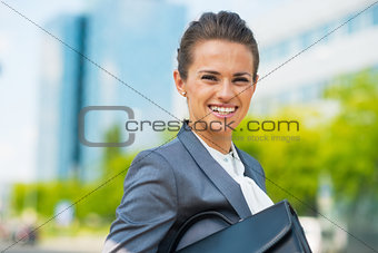 Portrait of smiling business woman with briefcase in office dist