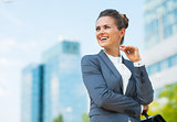 Smiling business woman with briefcase in office district looking