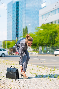 Business woman with briefcase in office district having pain in