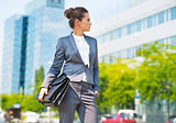 Happy business woman with briefcase in office district looking o