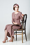 Lovely young woman sitting on chair. Portrait in retro style