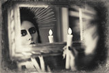 Beautiful goth girl holding candle in hand and looking into mirror. Grunge texture effect
