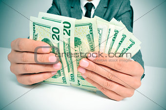 man in suit counting US dollar bills