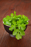 Fresh coriander in black bowl.