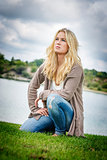 Blond woman kneeling at lake