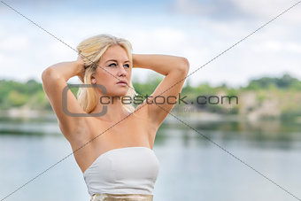 Blond girl outdoor portrait at lake