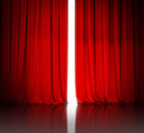 red theater or cinema curtain slightly open and white light behi