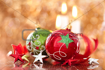 Christmas balls with stars and candles against holiday lights.