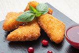 Fried cheese sticks served with cranberries, sauce on black ston