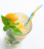 Glass of fresh lemonade with orange, ice cubes, mint, straws