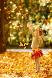 beautiful little girl in the autumn park playing in nature