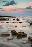 Summer landscape with rocks on beach during late evening and low