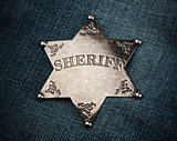 Sheriff star badge on blue denim background