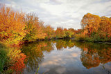 Landscape with colorful autumn trees reflected in the river
